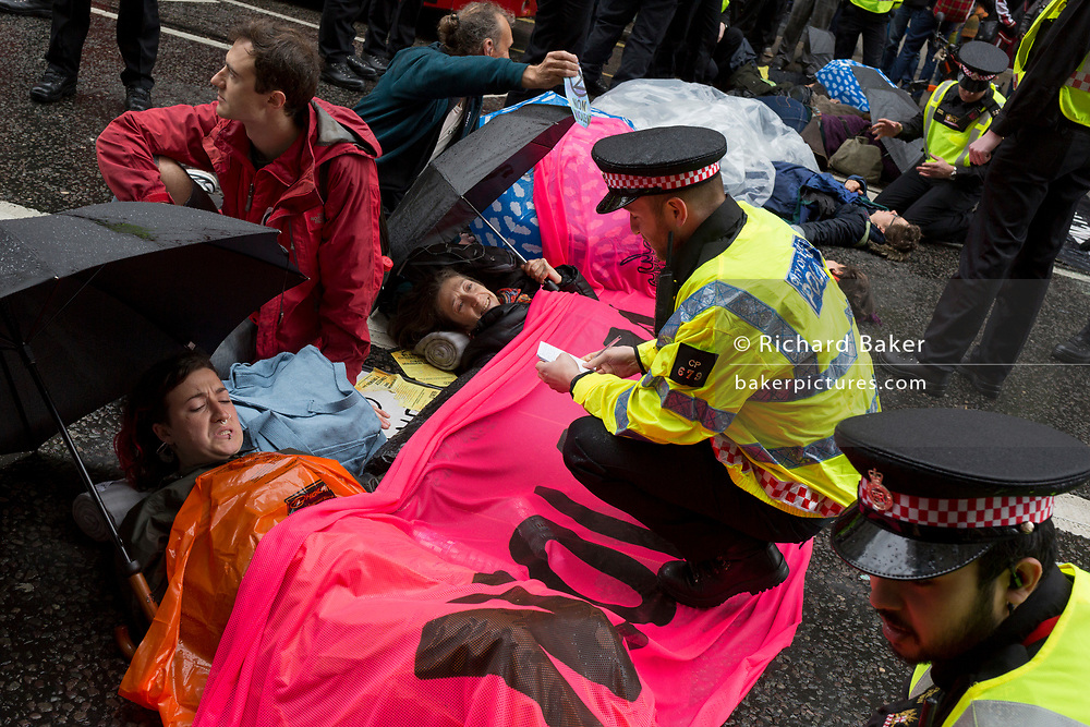 Environmental protesters chain themselves together and glue body parts to the road in Fleet Street on the 11th and final day of protests, road-blockages and arrests across London by the climate change campaign Extinction Rebellion, on 25th April 2019, in London, England.