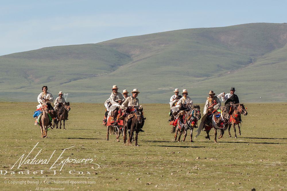 Northern Tibetans in traditional herdsmen dress with decorated horses. Tibet, Asia<br />