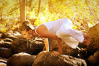 Woman in yoga posture outdoors in the forest.