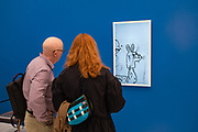 New York, NY - May 3, 2019. Spectators fascinated by a surreal video piece by Brian Bress at London's Josh Lilly Gallery at the Frieze Art Fair on New York City's Randalls Island.