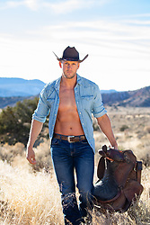 cowboy with open shirt holding a saddle outdoors