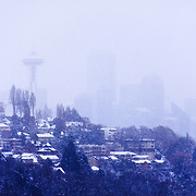 View of Space Needle and Seattle skyline from Ella Bailey Park in Magnolia neighborhood with Queen Anne Hill and downtown buildings during winter snow storm, Seattle, Washington USA