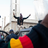 Anti-government protester jumps over a police car, in central Dakar, Senegal Friday, Feb. 17, 2012. Anti-government protesters and police clashed for a third consecutive day Friday, engaging in running street battles of rock throwing and tear gas in the streets of Dakar's downtown Plateau neighborhood. Demonstrators are defying a government ban on protests to call for the departure of 85-year-old President Abdoulaye Wade, who is running for a third term in next week's election.
