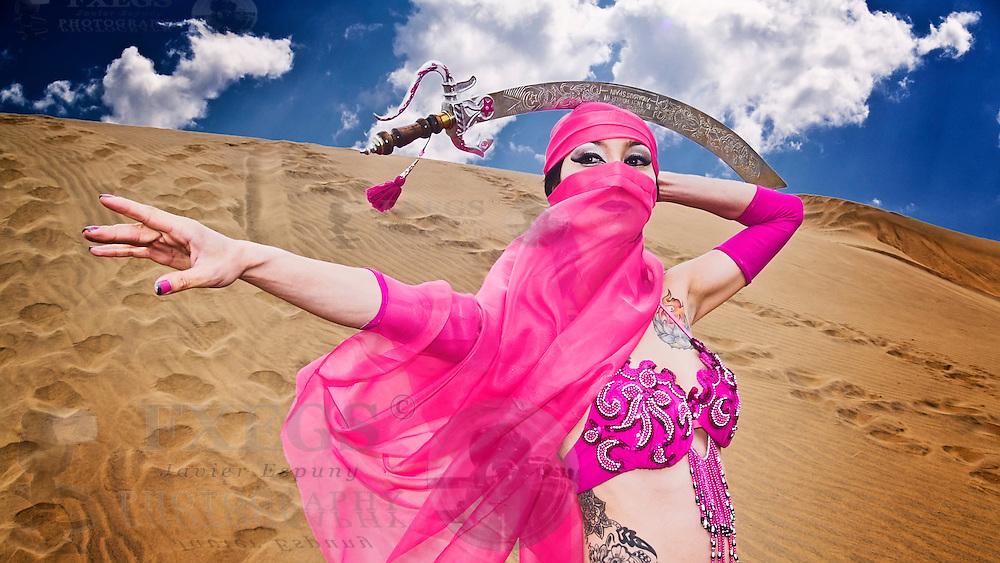Mujer joven en postura de danza árabe con espada sobre la cabeza y velo. Sesión en las dunas de Concón, Chile.