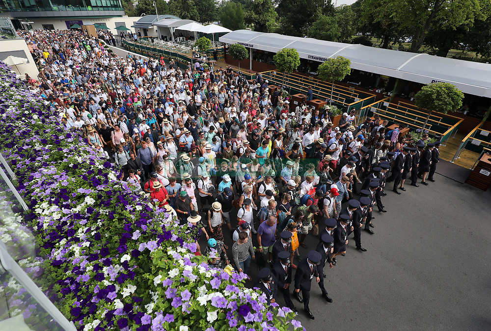 Spectators are led in during day two of the Wimbledon Championships at the All England Lawn Tennis and Croquet Club, Wimbledon.