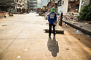 "03 DECEMBER 2012 - BANGKOK, THAILAND:    A worker rolls an oxygen tank down a deserted street in the ""Washington Square"" district in Bangkok. Washington Square was a notorious adult ""entertainment"" and red light district on Sukhumvit Soi 22 in Bangkok. Many of the bars and massage parlors catered in the district to older American and European men and opened in the 1960's when Bangkok was a ""R&R"" destination for American servicemen in Vietnam. It's being torn down to make way for new high rise hotels and condominiums.       PHOTO BY JACK KURTZ"