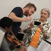 Aaron Phillips, left, and Margaret Anne Murphey shoot photos of the string class being taught at Tupelo Middle School as part of her video segment on the Tupelo Symphony for the Mississippi Bicentennial video being produced around the state.