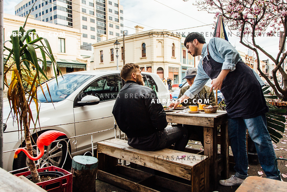 Diners being served by a waiter outside a cafe on Gertrude Street in Melbourne, Australia, September 1, 2017. Fitzroy has become one of the trendiest inner city suburbs in Australia with flourishing cafe's and niche restaurants. Asanka Brendon Ratnayake for the New York Times