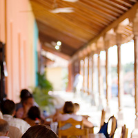 A girl drinks her coffee on a traditional veranda in Grnada, Nicaragua.