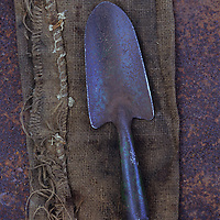 Well-used but slightly rusty garden trowel lying on hessian on  rusty metal sheet