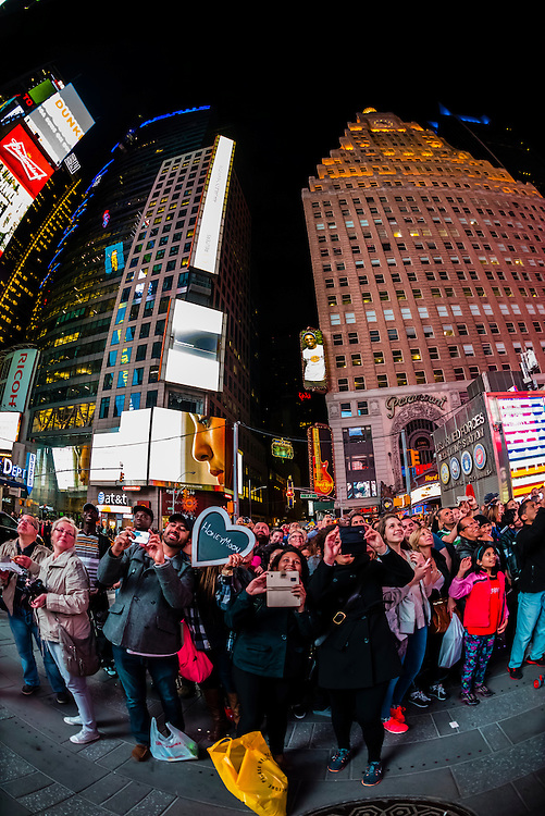 """Tourists appear on the Revlon """"Love is On"""" big screen in Times Square, New York, New York USA."""