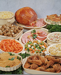 Family style buffet dinner table, featuring baked ham, fried chicken, fish filet, meat balls, carrots, mixed vegetables, buttered noodles, cole slaw, quiche,