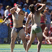 Players of knocked out teams who failed to score a try drink beer during their 'jocks run' during the Pub Charity Rugby Sevens 2012 New Zealand tournament at the Queenstown Recreation Ground, Queenstown, Otago, New Zealand. 8th January 2012. Photo Tim Clayton