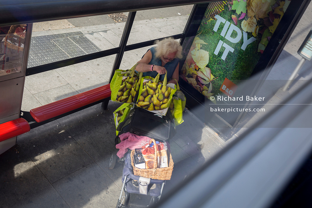 Alongside an ad for the B&Q DIY brand, an elderly lady holds two armfuls of shopping whilst waiting for the next bus at a bus stop at Elephant & Castle in Southwark, on 11th October 2018, in London, England.