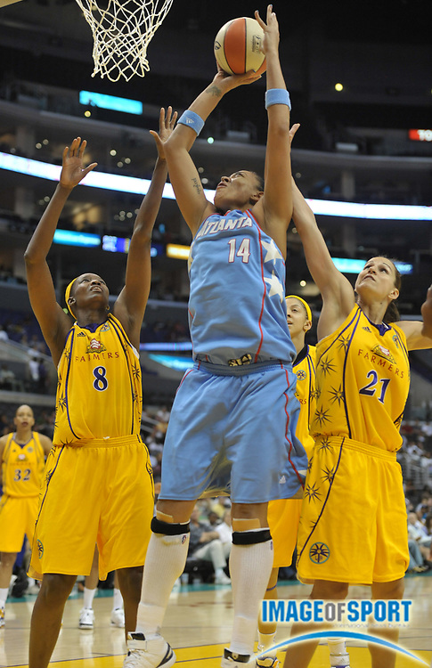 May 30, 2010; Los Angeles, CA, USA; Atlanta Dream center Erika de Souza (14) is defended by Los Angeles Sparks forward DeLisha Milton-Jones (8) and guard Ticha Penicheiro (21) in the second half at the Staples Center. The Dream defeated the Sparks 101-82.