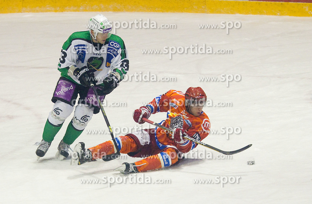 Damjan Dervaric of Olimpija vs Rok Ticar of Acroni during ice hockey match between HK Acroni Jesenice and  HDD Tilia Olimpija Ljubljana at 33rd Round of EBEL league, on January 1, 2011 in Arena Podmezakla, Jesenice, Slovenia. (Photo By Vid Ponikvar / Sportida.com)