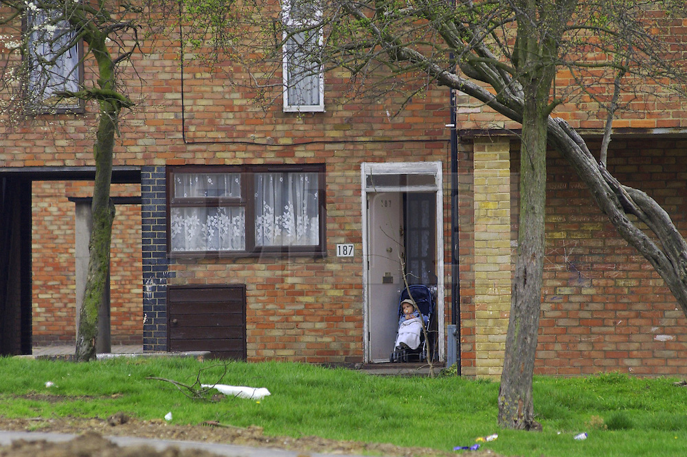 © Licensed to London News Pictures 04/05/2004.A baby in a pushchair sits at the doorway of a maisonette in Craylands estate, an impoverished council estate in Basildon, Essex..Basildon, UK.Photo credit: Anna Branthwaite