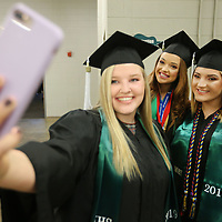Katelyn Harlow holds out her phone for a picture with classmates Kloey Thompson and Kaitlyn Cox as they wait to line up for the Mooreville High School graduation ceremony Saturday.