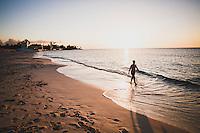 A woman walks along a beach during sunset, Nassau, Bahamas.