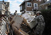 Members of the 192nd Engineer Battalion of Army National Guard from Stratford, Conn., clear debris from beach front property in the aftermath of Hurricane Irene in East Haven, Conn. (AP Photo/Jessica Hill)
