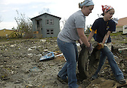 Two Kent State students carry a tire to a trash pile Tuesday, March 28, 2006 in Biloxi, Miss. Over 400 volunteers worked in Biloxi and the surrounding areas as part of Kent State University's alternative spring break. <br /> <br /> Photo by Pat Jarrett<br /> <br />  horizontal, biloxi, alternative spring break, student