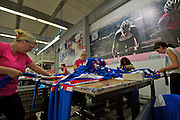 Employees at quality control station checking Russian Federation team kits--SMS