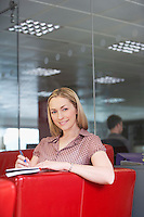 Female office worker sitting on sofa in office portrait