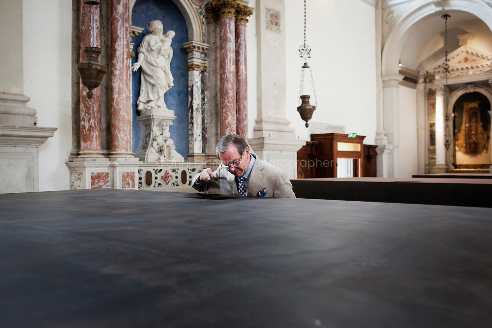 VENICE, ITALY - 29 MAY 2013: A man peers through a small aperture inside one of the six large iron boxes to see the diaroma contained within, part of &quot;S.A.C.R.E.D.&quot;, Ai Weiwei's new work shown at the Sant'Antonin's church in Venice, Italy, on May 29th 20113. <br /> <br /> &quot;S.A.C.R.E.D.&quot; (2013) is Ai Weiwei's new work addressing his 2011 arrest by the Chinese Government and the 81-day period subsequently spent in captivity. This is the first time the artist has directly responded to his incarceration through a work in a public exhibition. S.A.C.R.E.D. is composed of six parts: (i) S upper, (ii) A ccusers, (iii) C leansing, (iv) R itual, (v) E ntropy, and (vi) D oubt. This landmark work coprises six large iron boxes with small apertures - such as those found in the door of a cell - though which the viewer must peer to see the dioramas contained within. Each diorama includes large hyper-realist models of the artist and his captors, and documents the different stages of Ai Weiwei's time in incarceration.<br /> <br /> The 55th International Art Exhibition of the Venice Biennale takes place in Venice from June 1st to November 24th, 2013 at the Giardini and at the Arsenale as well as in various venues the city. <br /> <br /> Gianni Cipriano for The New York TImes