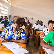 LÉGENDE: BTS génie civil 1ère année mécanique. Pendant la correction du devoir surveillé de mécanique et remises des copies aux étudiants. LIEU: CERFER, Lomé, Togo. PERSONNE(S): Des étudiants en train de faire leurs devoirs.