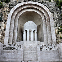 Monument aux Morts War Memorial in Nice, France <br /> Built into the side of a cliff in 1927 at the base of Colline du Ch&acirc;teau or Castle Hill is a 105 foot war memorial called Monument aux Morts.  It consists of an urn within a niche and two high reliefs: the left represents war and the right is for peace.  It honors over 3,600 men from Nice who died during World War I.  It is also a somber remembrance of the 1.5 million French people who lost their lives between 1914 and 1918.
