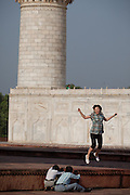 An Asian tourist is having a jumping picture taken inside the Taj Mahal complex, in Agra.