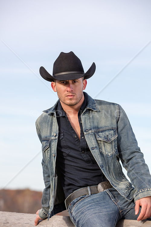 hot cowboy sitting on a  wooden fence on a ranch