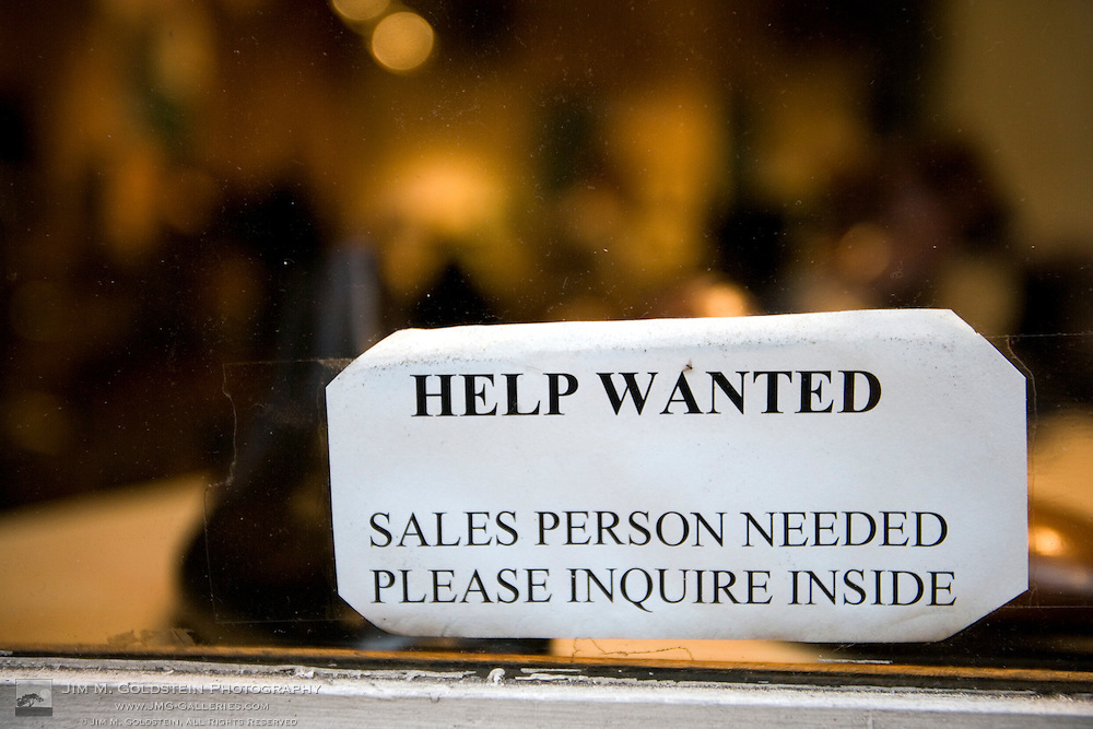 A help wanted sign for a sales person on a store window in New York city