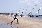 Runners race to their Dhows to begin the Dhow races across the bay between Manda Island and Lamu, Kenya.