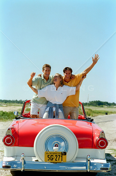 three friends in a vintage car outdoors having fun together