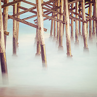 Beach pier posts retro photo. Underneath a California pier along the Pacific Ocean. Copyright ⓒ 2017 Paul Velgos with All Rights Reserved.