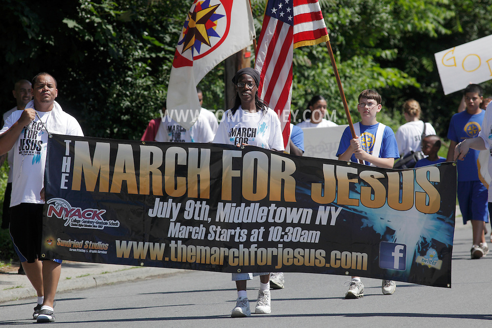 Middletown, New York - People with banners, flags and signs parade on the street during a March for Jesus on  July 9, 2011.