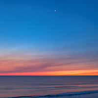 Venus and a crescent moon, with the pre-dawn clouds and ocean colors, overlooking the Marconi Beach. Part of the Cape Cod National Seashore, Massachusetts
