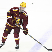 Sam Warning #11 of the Minnesota Gophers warms up on the ice prior to the game against the Northeastern Huskies at Matthews Arena on November 29, 2014 in Boston, Massachusetts. (Photo by Elan Kawesch)