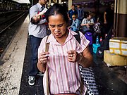 02 JANUARY 2019 - BANGKOK, THAILAND:      A woman studies her ticket while she waits for a train bound for Trang in Hua Lamphong Train Station in Bangkok. The train and bus stations in Bangkok were crowded Wednesday with people going home after the long New Year's weekend.      PHOTO BY JACK KURTZ