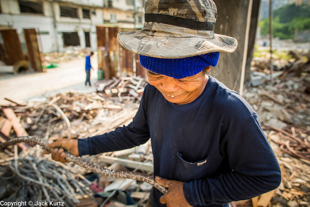 """11 DECEMBER 2012 - BANGKOK, THAILAND:  A worker recycles rebar in a building at """"Washington Square"""" a notorious entertainment district off Sukhumvit Soi 22 in Bangkok. Demolition workers on many projects in Thailand live on their job site tearing down the building and recycling what can recycled as they do so until the site is no longer inhabitable. They sleep on the floors in the buildings or sometimes in tents, cooking on gas or charcoal stoves working from morning till dark. Sometimes families live and work together, other times just men. Washington Square was one of Bangkok's oldest red light districts. It was closed early 2012 and is being torn down to make way for redevelopment.    PHOTO BY JACK KURTZ"""