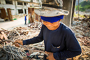"11 DECEMBER 2012 - BANGKOK, THAILAND:  A worker recycles rebar in a building at ""Washington Square"" a notorious entertainment district off Sukhumvit Soi 22 in Bangkok. Demolition workers on many projects in Thailand live on their job site tearing down the building and recycling what can recycled as they do so until the site is no longer inhabitable. They sleep on the floors in the buildings or sometimes in tents, cooking on gas or charcoal stoves working from morning till dark. Sometimes families live and work together, other times just men. Washington Square was one of Bangkok's oldest red light districts. It was closed early 2012 and is being torn down to make way for redevelopment.    PHOTO BY JACK KURTZ"