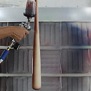 Amy Tucci spray painting a bat in the spray booth at Tucci Lumber Company, which makes baseball bats. Norwalk, Connecticut, USA. 27th June 2014. Photo Tim Clayton
