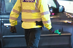 """© Licensed to London News Pictures . 23/12/2017. Manchester, UK. A police officer picks a broken bottle from the pavement and carries it away to a waste bin . Revellers out in Manchester City Centre overnight during """" Mad Friday """" , named for being one of the busiest nights of the year for the emergency services in the UK . Photo credit: Joel Goodman/LNP"""