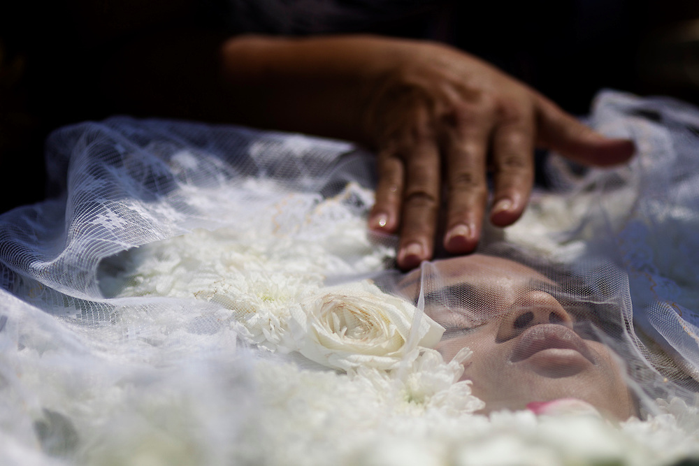 Relatives and friends mourns over the body of Luiza Paula da Silveira Machado, 14 years-old, during her funeral at Jardim da Saudade cemetery in Rio de Janeiro, Brazil, Friday April 8, 2011. <br /> <br /> Luiza was one of the 12 children kiiled by a gunman who opened fire in an elementary school in Rio de Janeiro.