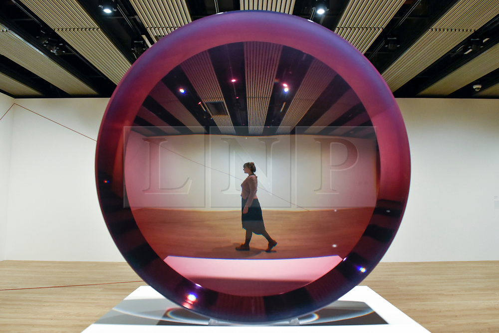 """© Licensed to London News Pictures. 25/09/2018. LONDON, UK. A gallery staff member walks by """"Untitled (Parabolic Lens)"""", 1971, by Fred Eversley. Preview of """"Space Shifters"""" at the Hayward Gallery, an exhibition which features artworks by 20 leading international artists that disrupt the visitor's sense of space and alter their perception of their surroundings.  The show runs 26 September to 6 January 2019.  Photo credit: Stephen Chung/LNP"""