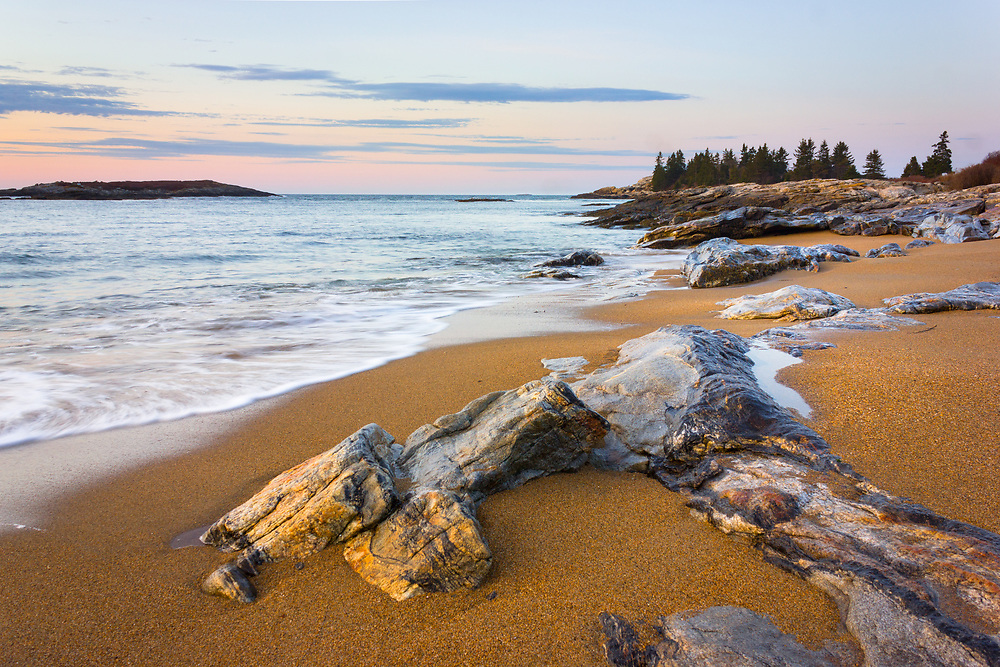 The surf washes gently along golden sand and colorful stones along the beach at Reid State Park.