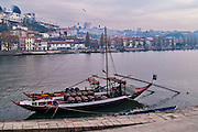 Oporto, December 2012. A boat docked at Douro river loaded with barrels. Vila Nova de Gaia on background.