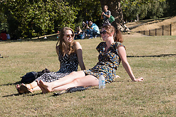 © Licensed to London News Pictures. 11/09/2016. LONDON, UK.  Two women sunbathe and enjoy the hot and sunny autumn weather and the city of London skyline in Greenwich Park, south east London today.  Photo credit: Vickie Flores/LNP