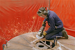 Man using circle grinder at engineering works,